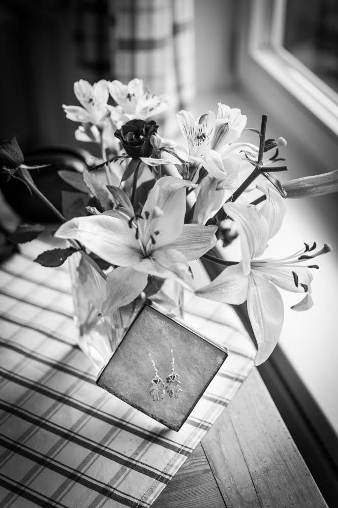 Foto von den Ohrringen der Braut vor einem Blumenstrauß